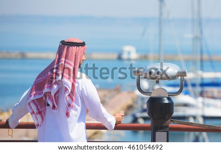 Arabian man looking at the yacht harbor, back view