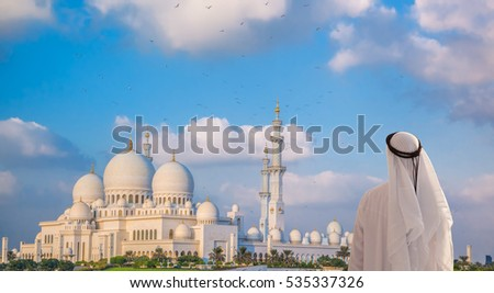 Arabian man watching Sheikh Zayed Grand Mosque in Abu-Dhabi, United Arab Emirates