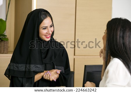 Arabian Receptionist helping a customer on the front desk - stock photo