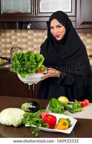 Arabian woman holding a bowl of veggies for salad preparation - stock photo