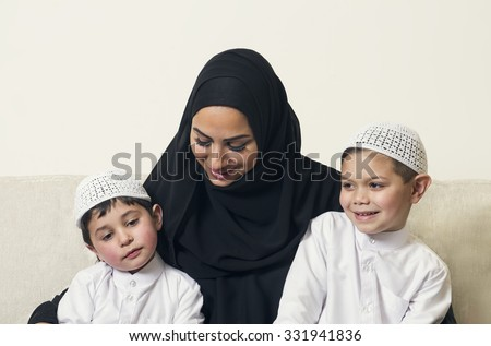 Arabian woman holding her children, mother and sons sitting on the couch in their living room  - stock photo