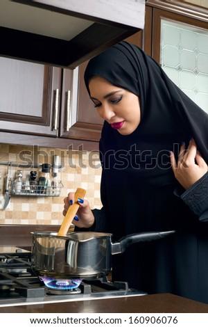 Arabian woman stirring food in the casserole - stock photo