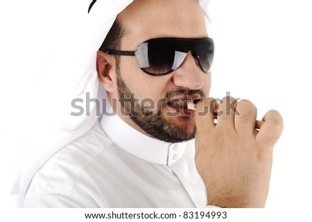 Arabic adult cleaning teeth with miswak - stock photo