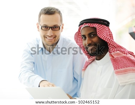 Arabic black and caucasian men working together on laptop - stock photo