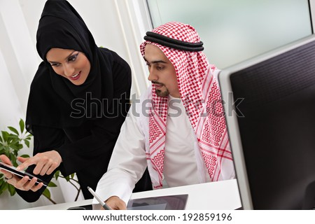 Arabic business couple working in office using tablet and computer. - stock photo