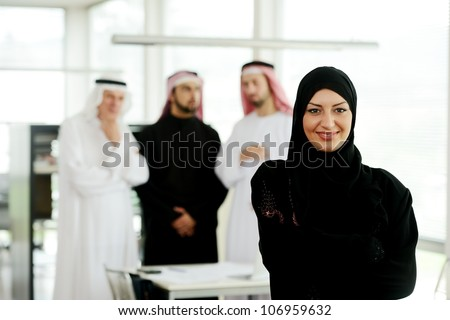Arabic business woman working in team with her colleagues at office - stock photo