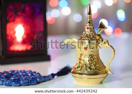 Arabic Coffee pot, Muslim prayer beads and lantern with colorful out of focus light as background. Ramadan, Eid concept  - stock photo