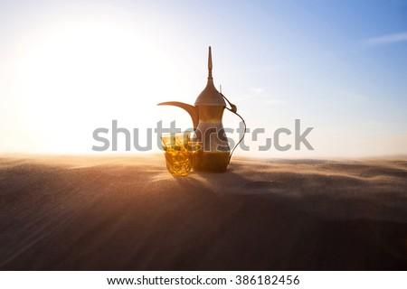 Arabic Coffee pot on desert dunes - stock photo