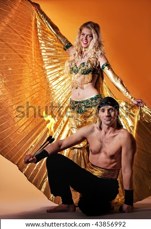 Arabic dancer with a handsome men performing fire show - stock photo