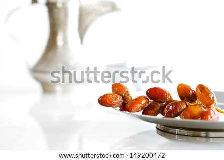 Arabic dates on a white plate with Arabic coffee pot of the Bedouin on a white background - stock photo