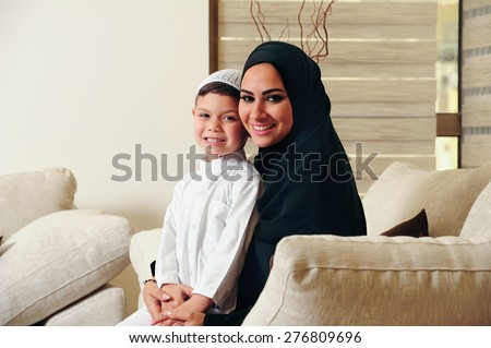 Arabic family, mother and son sitting on the couch in their living room - stock photo