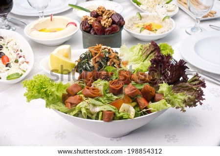Arabic food of fattoush and hommos cheese and dates served during Ramadan - stock photo