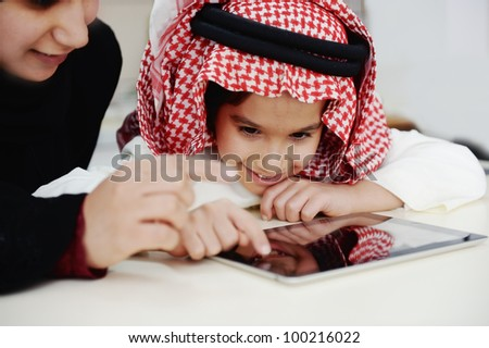 Arabic little boy and his mother working with touch tablet - stock photo