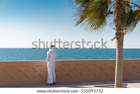 Arabic man is on the waterfront and looking at the sea