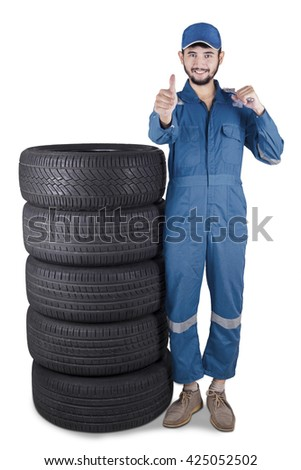 Arabic mechanic holding a wrench and showing thumb up while standing next to a pile of tires
