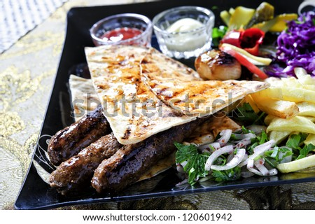Arabic mixed barbeque plate with sauces and multiple garnish - stock photo