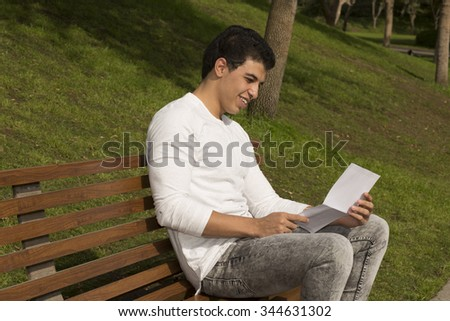 Arabic Model Sitting outdoor Studding on Green area with the laptop theme  - stock photo