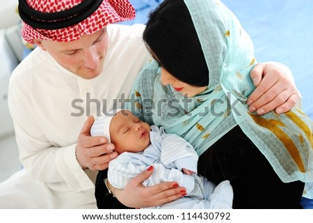 Arabic Mother and Father with baby at home - stock photo
