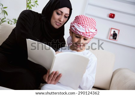 Arabic Mother And Son Together Sitting On The Couch And Reading A Book. - stock photo