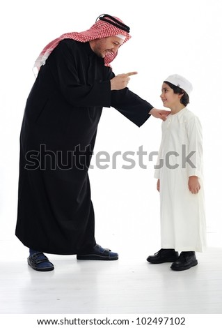 Arabic Muslim father and son standing together - stock photo