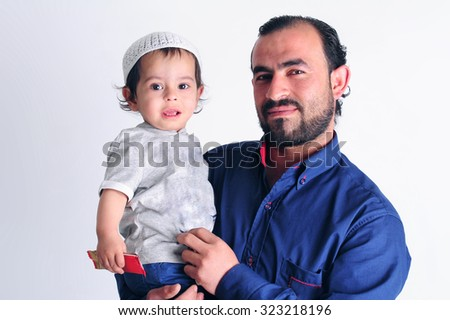 Arabic Muslim father holding his son  - stock photo