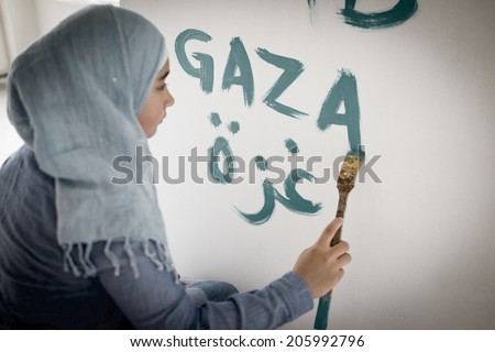 Arabic Muslim girl writing messages on board - stock photo