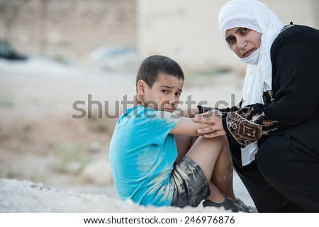 Arabic Muslim Middle Eastern poor woman with her son on dirty ground
