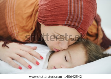 Arabic Muslim mother kissing her baby while sleeping