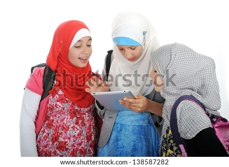 Arabic Muslim school girls working together on tablet pc