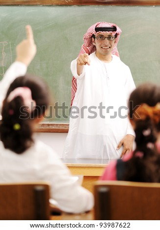 Arabic Muslim teacher in classroom with children. Competition and success. - stock photo