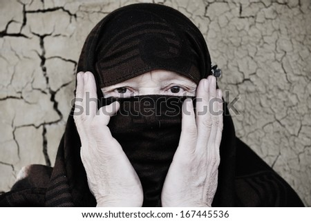 Arabic Muslim woman on cracked wall - stock photo