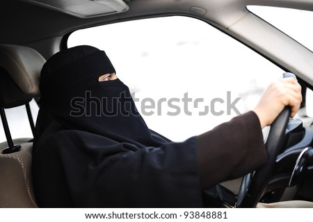 Arabic Muslim woman with veil and scarf (hijab and niqab) driving car - stock photo