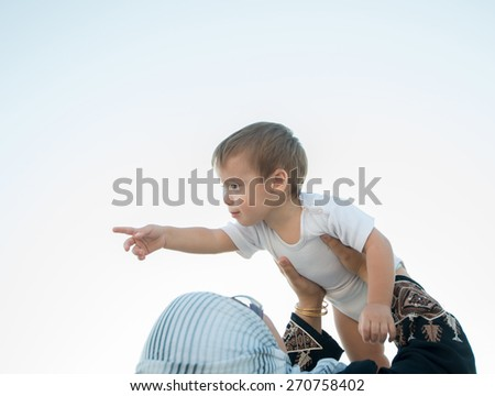 Arabic woman holding baby in air and playing - stock photo