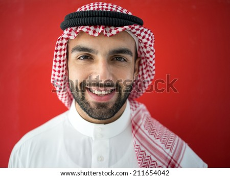 Arabic young businessman posing on red wall - stock photo