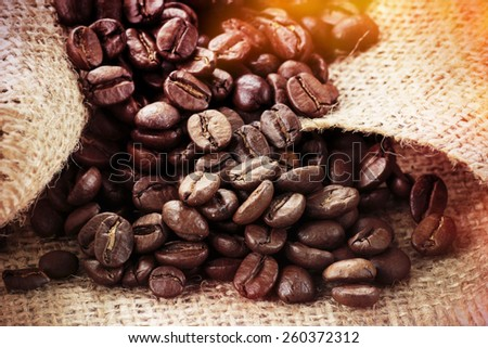 Arabica coffee beans on burlap background. Post processed with vintage filter.