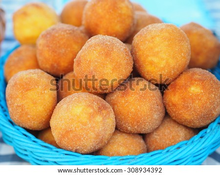Arancini - Fried rice balls with saffron filled with prosciutto and cheese in a blue wicker basket - unusual specialty. - stock photo