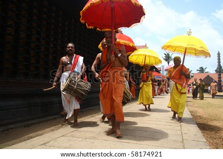 ARANMULA, INDIA - JULY 31 : Devotees with colorful umbrellas taking holy procession around the temple JULY 31, 2010 in Aranmula, Kerala, India. - stock photo