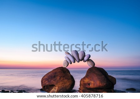 Arc between of the red stones on the seashore - stock photo