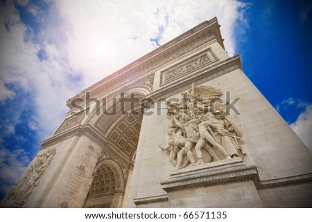 Arc de Triomphe (arch of triumph) in Paris, on a blue sky - stock photo