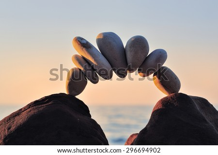Arc of pebbles between of the stones on the coast - stock photo