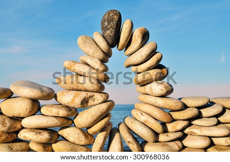 Arc of pebbles between of the stones on the seashore - stock photo