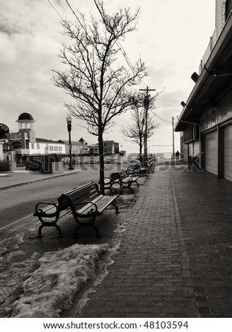 Arcade area of Old Orchard Beach abandoned for the winter except for one lone walker in the distance - stock photo