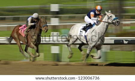 """ARCADIA, CA - DEC 26: Rafael Bejarano (black cap) and """"Book Review"""" move up on the far turn to overtake the lead horses and win The La Brea Stakes at Santa Anita Park on Dec 26, 2012 in Arcadia, CA. - stock photo"""