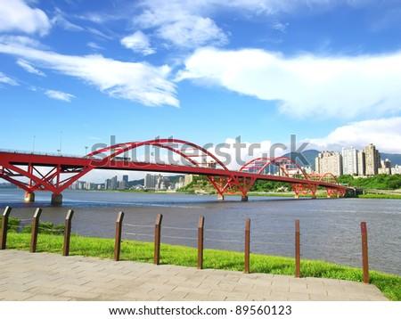Arch bridge and river bank - stock photo