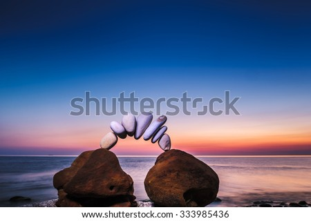 Arch of pebbles between of stones on the seashore - stock photo