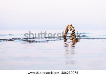 Arch of pebbles on the sea surface - stock photo
