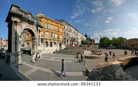 Arch of the Sergeii on Portarata square with people passing. - stock photo