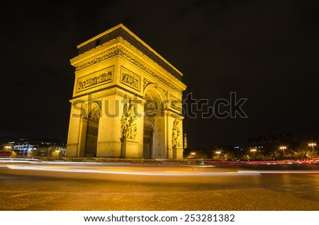 Arch of Triumph of the Star (Arc de Triomphe de l'Etoile) in Paris (France) at night. Trail of traffic lights in the foreground. One of main representative symbols of French capital city. - stock photo