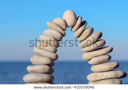 Arch of white pebbles on sea background - stock photo