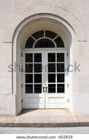 Arched doorway on historic building - stock photo